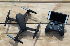 Quadcopter negro del abejón con un teledirigido y teléfono en la tabla de madera Imagen de archivo