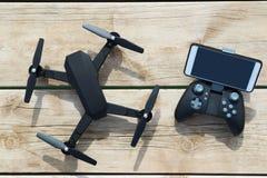 Quadcopter negro del abejón con un teledirigido y teléfono en la tabla de madera Fotos de archivo
