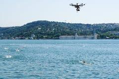 Quadcopter quita un calor en el agua abierta de nadadores con el estrecho de Bosphorus Verano en Estambul, Turquía Fotos de archivo