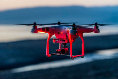 Quadcopter at a red light. Quadcopter in red light against the background of sea and mountains Stock Photography