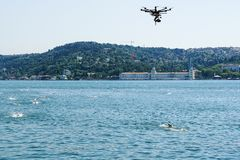 Quadcopter removes a heat on open water of swimmers through the Bosphorus strait. Summer in Istanbul, Turkey. Quadcopter removes a heat on open water of Stock Photos