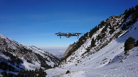 The quadcopter weighs in the air in the mountains. Mavic flies in the mountains. View of the gorge, blue sky and snowy mountains. A small drone in the stock image