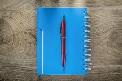 Quaderno di spirale della penna del biro sul bordo di legno Fotografia Stock