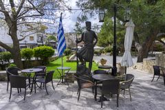 Quadrado central da vila de Archanes com as cafetarias tradicionais Estátua de bronze de um herói cretan fotos de stock