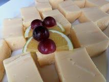 Quadrados deliciosos do caramelo decorados com uvas e fatias do limão foto de stock royalty free