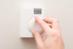 Quadrante di tornitura della mano sul termostato fissato al muro Fotografia Stock Libera da Diritti