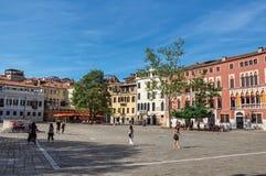 Quadratische Ansicht von bunten Altbauten, von Restaurants und von Leuten in Venedig Stockbild