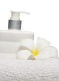 Quadratische Flaschenseife und -blume auf weißem Tuchweißhintergrund lizenzfreies stockbild