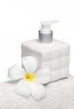 Quadratische Flaschenseife und -blume auf weißem Tuchweißhintergrund lizenzfreie stockfotografie