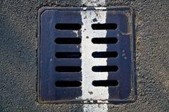 Quadratische Metallluke in der städtischen Pflasterung, Abwasserkanalkanaldeckel mit Markierung zeichnet Lizenzfreie Stockfotos