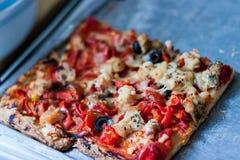 Quadratische Scheibe der Pizza auf einem grauen Zinnbehälter lizenzfreie stockfotos