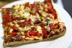 Quadratische Scheibe der Pizza auf einer weißen Platte lizenzfreie stockbilder