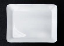 Quadratische weiße Platte lokalisiert auf schwarzem Hintergrund Lizenzfreies Stockbild