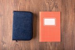 Quadratischer Übungsbuch- und -bleistiftkasten auf hölzernem Hintergrund Stockfotografie