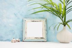 Quadratischer blauer Fotorahmenspott oben mit grünen tropischen Anlagen in vaseand kleinen Holzhäusern auf Regal Skandinavische A stockfotografie