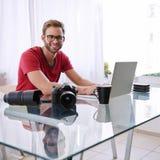 Quadratischer Schuss eines jungen Fotografen, der an der Kamera lächelt Lizenzfreies Stockfoto