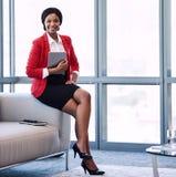 Quadratisches Bild der Geschäftsfrau lächelnd an der Kamera im businesslounge lizenzfreie stockfotografie