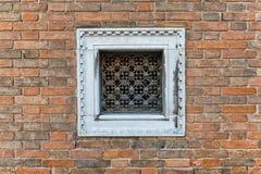 Quadratisches kleines Fenster mit weißem Rahmen auf Backsteinmauer Stockfoto