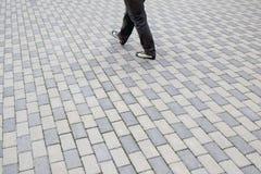 Quadratisches Muster der Kopfsteine, die Frauen gehen weg Lizenzfreie Stockfotografie