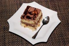 Quadratisches Stück des Kuchens mit Schokolade und Mandel auf der weißen Platte stockbild