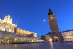 Quadrato del mercato a Cracovia al tramonto Sukiennice e Ratusz poland Immagine Stock