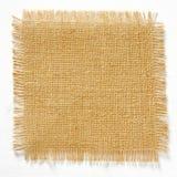Quadrato della tela di iuta della tela da imballaggio con i bordi sfilacciati isolati Immagine Stock