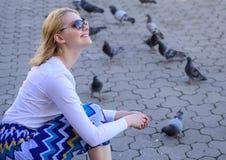 Quadrato di città di rilassamento della donna bionda della ragazza e piccioni d'alimentazione Il tiro del turista o del cittadino immagine stock libera da diritti