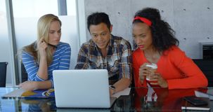 Quadri che si siedono alla tavola e che lavorano al computer portatile in ufficio moderno 4k video d archivio