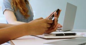 Quadri che utilizzano telefono cellulare e computer portatile nell'ufficio 4k archivi video