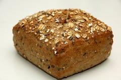 Quadri il rullo di pane, coperto in avena e semi fotografie stock libere da diritti