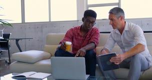 quadri maschii Multi-etnici che discutono sopra il computer portatile nell'ufficio moderno 4k archivi video