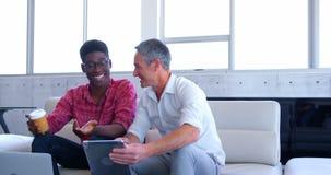 quadri maschii Multi-etnici che discutono sopra il computer portatile nell'ufficio moderno 4k video d archivio