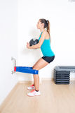 Quadriceps Eccentric Training with Russian belt. Sexy woman functional training exercise with medicine ball Royalty Free Stock Images