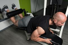 Quadriceps And Glutes Exercise In A Gym. Strong Man In The Gym And Exercising Quadriceps And Glutes On Machine - Muscular Athletic Bodybuilder Fitness Model Stock Image