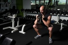 Quadriceps And Glutes Exercise In A Gym. Strong Man In The Gym Exercising Quadriceps And Glutes With Dumbbells - Muscular Athletic Bodybuilder Fitness Model Royalty Free Stock Photography