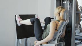 Quadricipite delle gambe di addestramento della donna sull'apparecchiatura di addestramento video d archivio