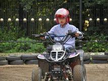 在孩子的quadricycle的男孩骑马,获得乐趣 库存照片
