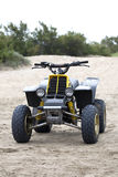 Quadricycle in the sand. Yellow quadricycle in the sand Royalty Free Stock Photos