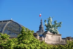 Quadriga statue on top of the Grand Palais in Paris. Quadriga statue on top of the Grand Palais in Paris on a bright day in Spring. Focus on the statue, space Stock Photo