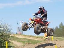 Quadrilátero de Moto que salta do monte Fotografia de Stock Royalty Free
