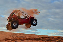Quadrilátero de salto do homem através do ar na duna de areia fotografia de stock royalty free