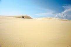 Quadrilátero que Biking em dunas de areia fotografia de stock royalty free
