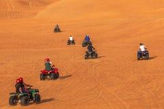 """Quadrilátero que Biking turistas do †da excursão da aventura de Dubai """"que têm o divertimento na equitação da bicicleta do quad imagem de stock royalty free"""