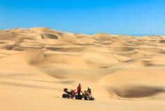 Quadrilátero que conduz povos - dois motociclistas felizes na areia abandonam Fotos de Stock Royalty Free