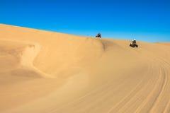 Quadrilátero que conduz povos - dois motociclistas felizes na areia abandonam Foto de Stock Royalty Free