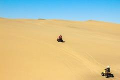 Quadrilátero que conduz povos - dois motociclistas felizes na areia abandonam Fotografia de Stock Royalty Free