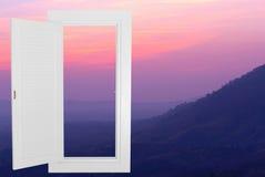 Quadro aberto da janela branca com fundo do moutain do por do sol Fotos de Stock