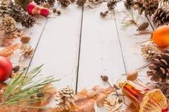 Quadro abstrato do Natal com cones, casca do pinho, bolotas, e brinquedos Fundo de madeira branco Imagem de Stock