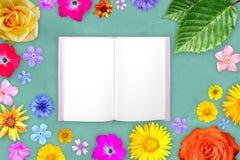 Quadro bonito da flor com bloco de notas no centro na cerceta, fundo mar-verde do papel de embalagem Composição floral da mola ou foto de stock