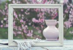 Quadro branco, jarro da porcelana, copo e guardanapo cor-de-rosa em uma tabela do wh Foto de Stock Royalty Free